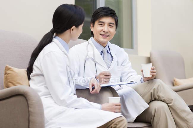 Médicos chineses conversando no hospital com café — Fotografia de Stock