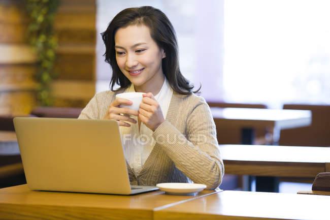 Donna cinese che utilizza il computer portatile in caffetteria — Foto stock