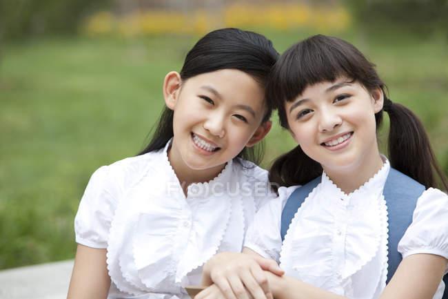Studenti in uniforme scolastica seduti fianco a fianco — Foto stock