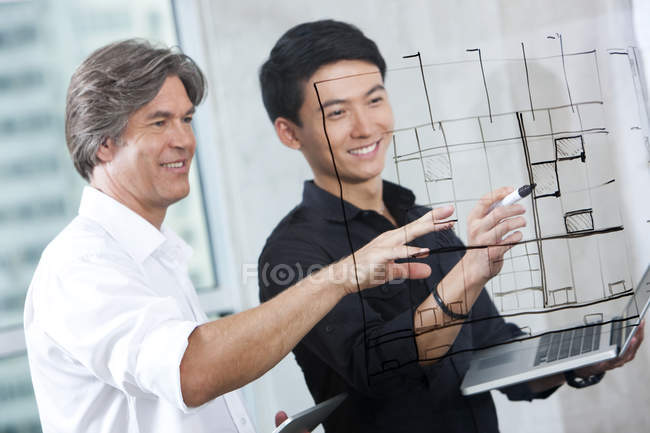 Male designers drawing sketch on glass wall — Stock Photo