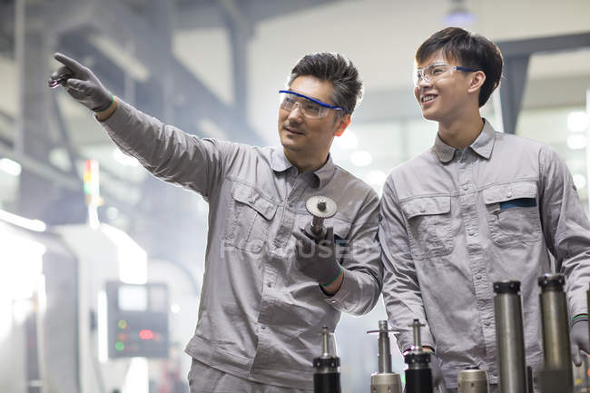 Chinese engineers working with machine parts at factory — Stock Photo