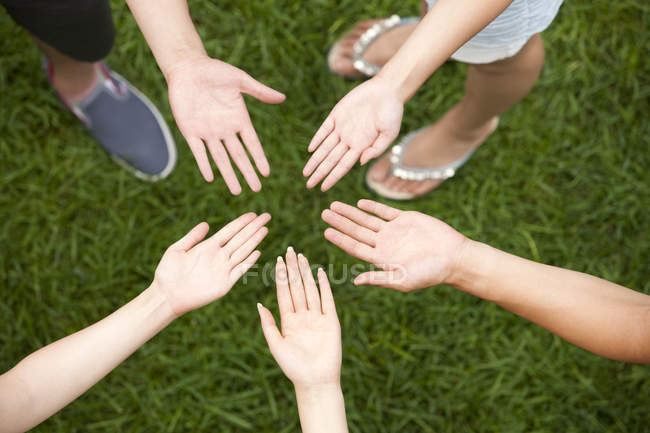 Cropped view of friends putting hands together — Stock Photo