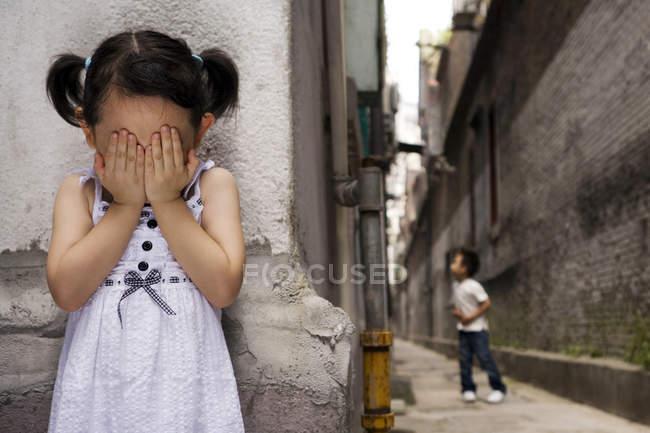 Olhos de cobertura menina chinesa enquanto brincava de esconder e procurar — Fotografia de Stock