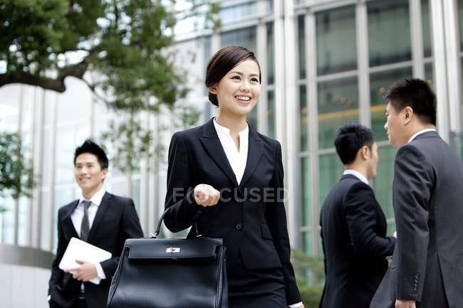 Chinese businesswoman holding briefcase on street with businessmen — Stock Photo