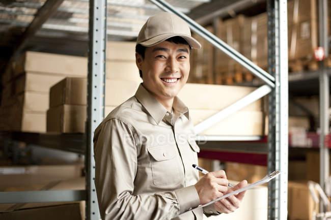 Trabajador almacén chino con portapapeles - foto de stock