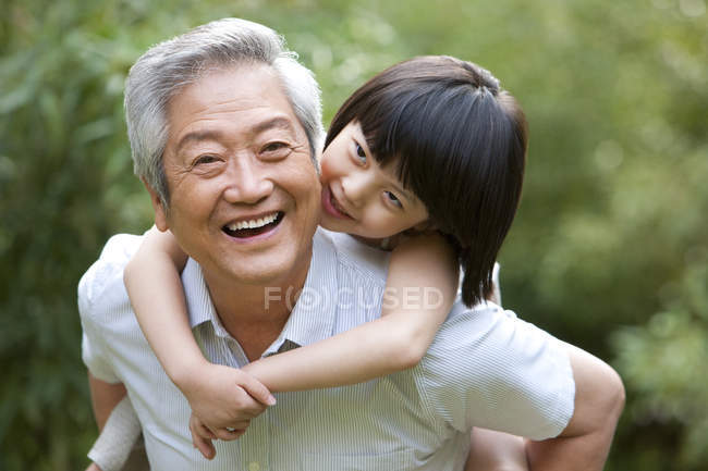 Chinese girl embracing grandfather from behind in garden — Stock Photo