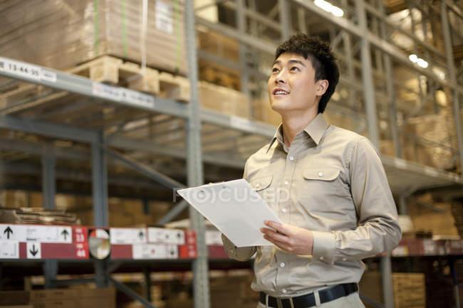 Trabajador almacén chino con portapapeles buscar - foto de stock