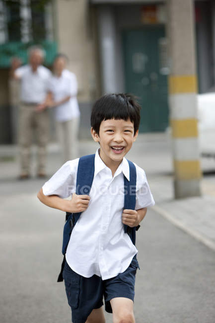 Chinese schoolboy running on street with grandparents in background — Stock Photo