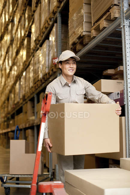 Chinese warehouse worker carrying cardboard boxes — Stock Photo