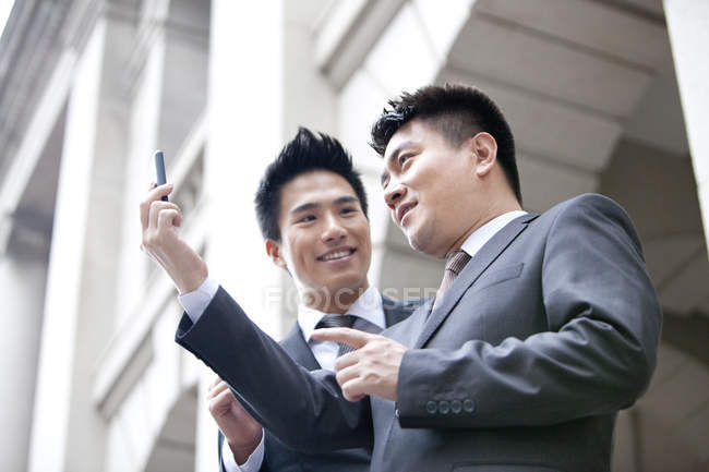 Chinese business colleagues using smartphone on street — Stock Photo
