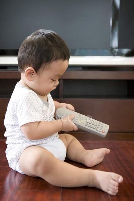 Chinois de bébé garçon tenant la télécommande — Photo de stock