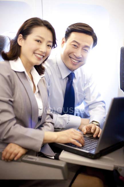 Китайський ділових людей сидять з ноутбука на площині місць — стокове фото