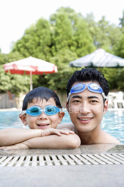 Chinese father and son in swimming goggles at pool — Stock Photo
