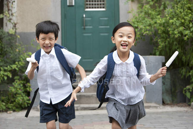 Chinese children running with ice pops on street — Stock Photo