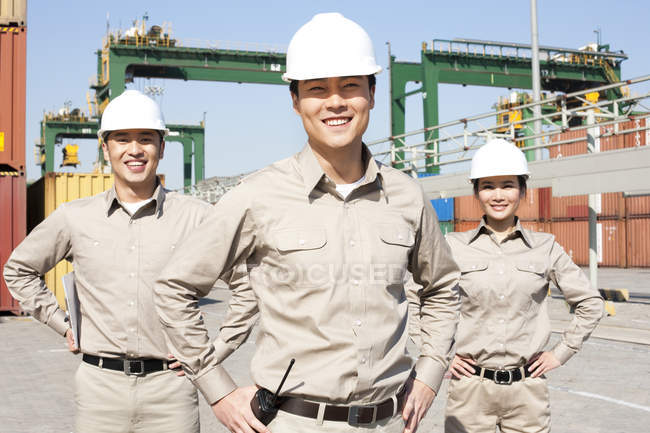 Chinese shipping industry workers with hands on hips — Stock Photo