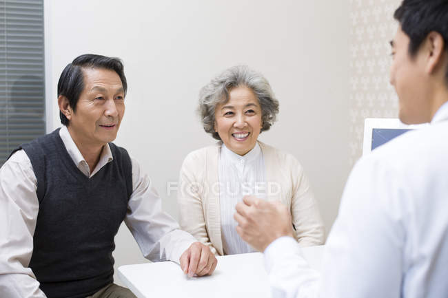 Chinese doctor explaining dosage of medicine to senior couple — Stock Photo