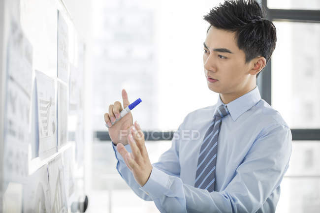 Chinese businessman working with whiteboard in office — Stock Photo