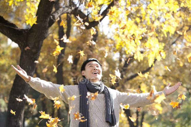 Chinese man enjoying falling autumn leaves in park — Stock Photo