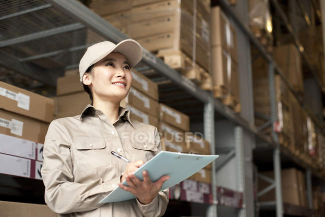 Chinese warehouse worker with clipboard looking up — Stock Photo