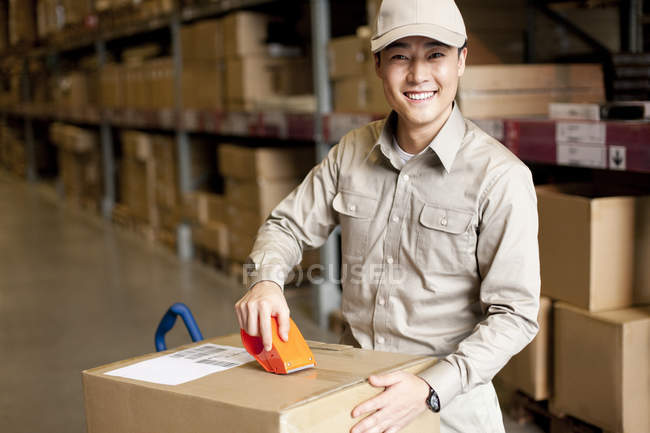 Male Chinese warehouse worker packing box — Stock Photo