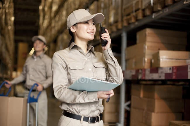 Male and female Chinese manual workers with walkie-talkie in warehouse — Stock Photo