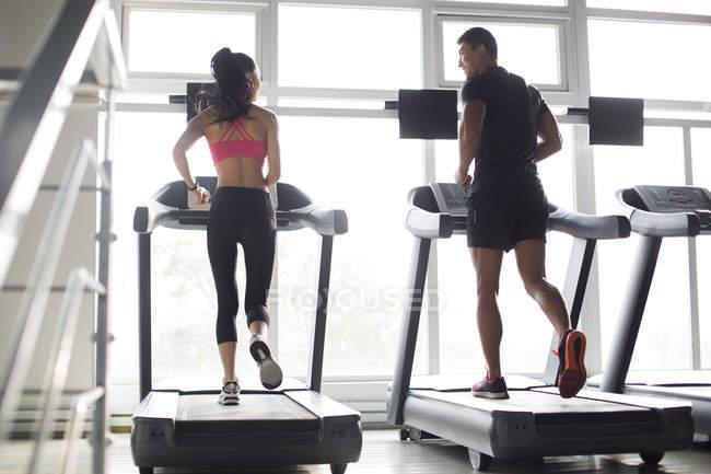 Китайская пара тренируется на беговых дорожках в тренажерном зале — стоковое фото