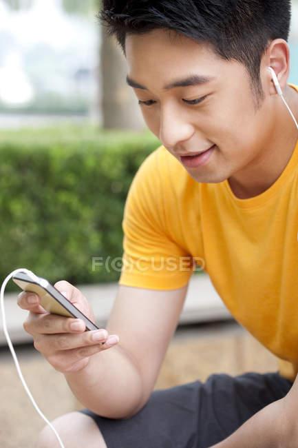 Cinese in auricolari utilizzando smartphone e amico — Foto stock
