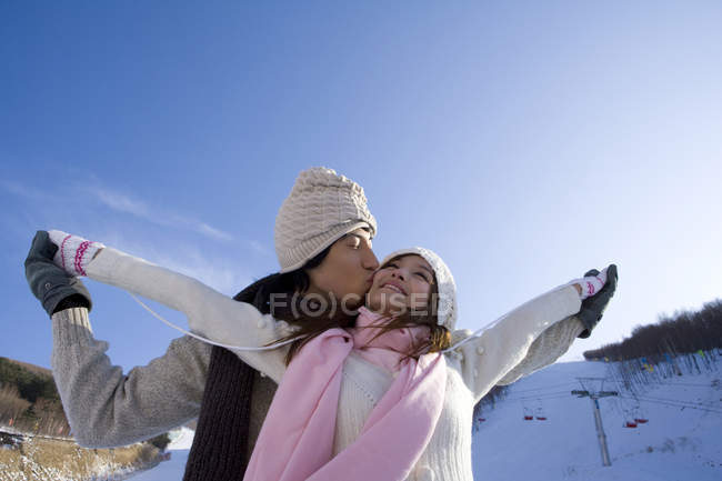 Chinese man kissing woman with arms outstretched — Stock Photo