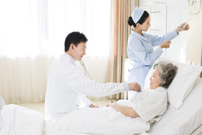 Médecin chinois à l'aide du stéthoscope sur le patient à l'hôpital — Photo de stock