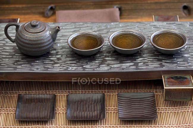 Tasses de thé et théière chinoises avec boisson dans une rangée — Photo de stock