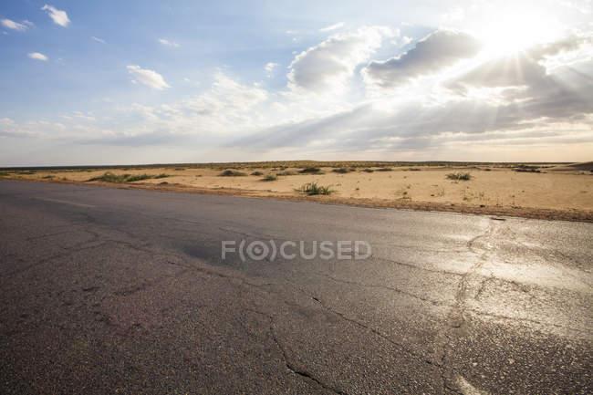 Straße, die durch Wüste tagsüber in der chinesischen Provinz Innere Mongolei — Stockfoto