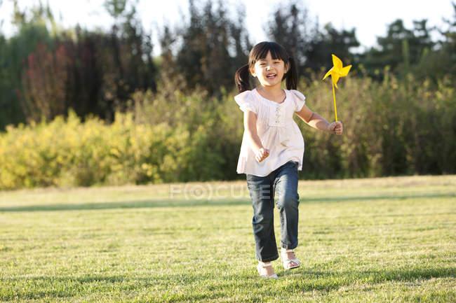 Pequena menina chinesa correndo no prado com pinwheel — Fotografia de Stock
