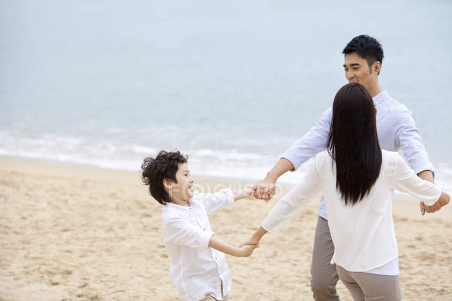 Chinese parents with son having fun on beach — Stock Photo