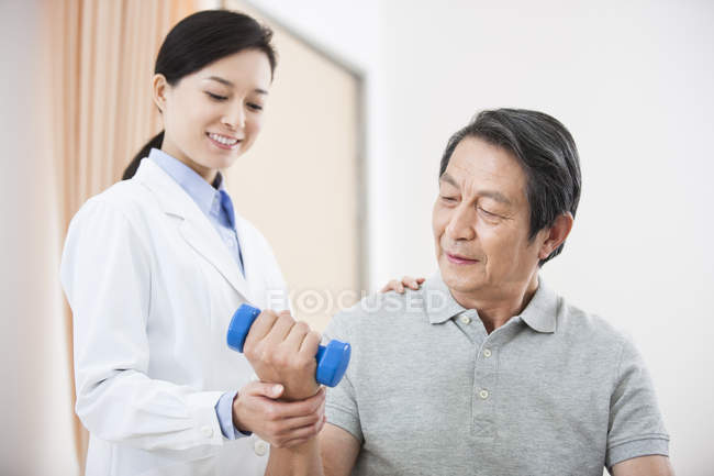 Senior patient exercising with dumbbell with doctor assistance — Stock Photo