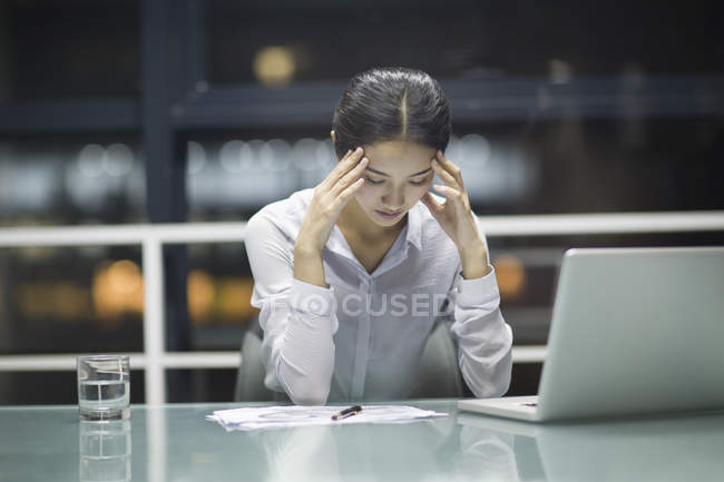 Cansado empresária chinesa massageando testa no escritório — Fotografia de Stock