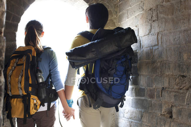 Rear view of couple of hikers in ancient ruins arch — Stock Photo
