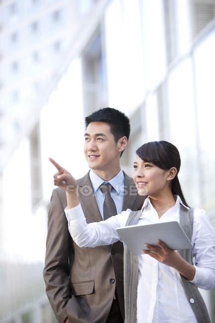 Китайский бизнес-леди с коллегой, указывая и проведение цифровые таблетки — стоковое фото