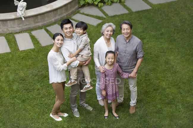 Vista de ángulo alto de la familia china mirando hacia arriba en el césped verde - foto de stock
