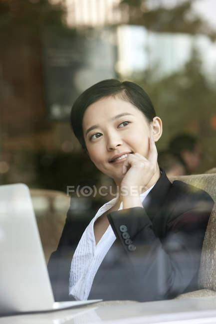 Donna di affari con la mano sul mento che guarda attraverso la finestra nella caffetteria — Foto stock