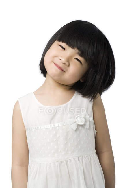 Retrato de una niña china inclinando la cabeza sobre fondo blanco - foto de stock