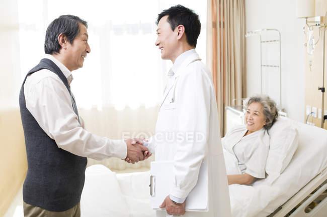 Homme chinois serrant la main de docteur avec une femme dans son lit d'hôpital — Photo de stock