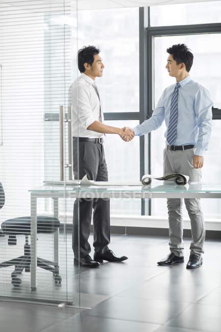 Молодые китайские бизнесмены пожимают руки в офисе — стоковое фото
