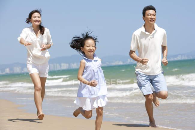 Китайская семья работает на солнечном пляже — стоковое фото