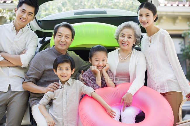 Chinese businessman holding son on street with family — Stock Photo