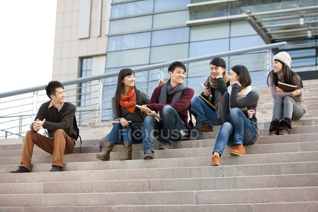 Chinese college students sitting on steps of university building — Stock Photo