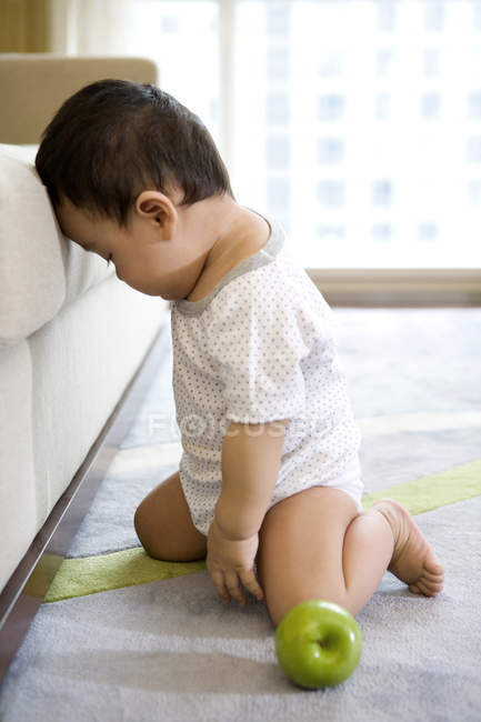 Chinese infant sitting on carpet and pressing forehead to sofa — Stock Photo