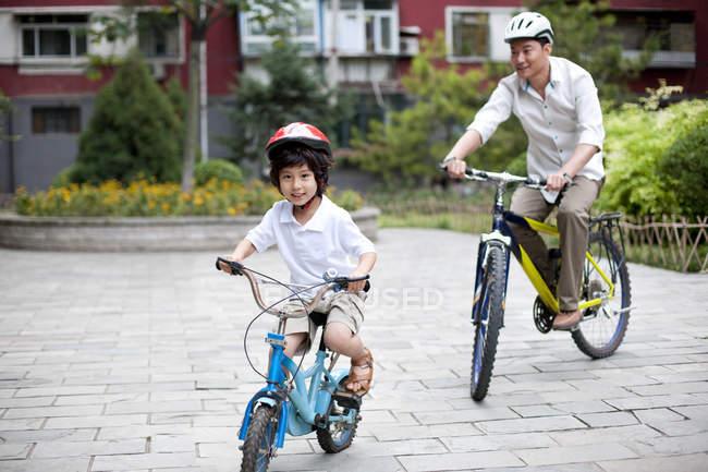 Chinês pai e filho andar de bicicleta no bairro residencial — Fotografia de Stock