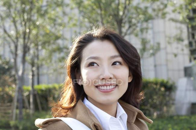 Retrato de una mujer china sonriente en la ciudad - foto de stock