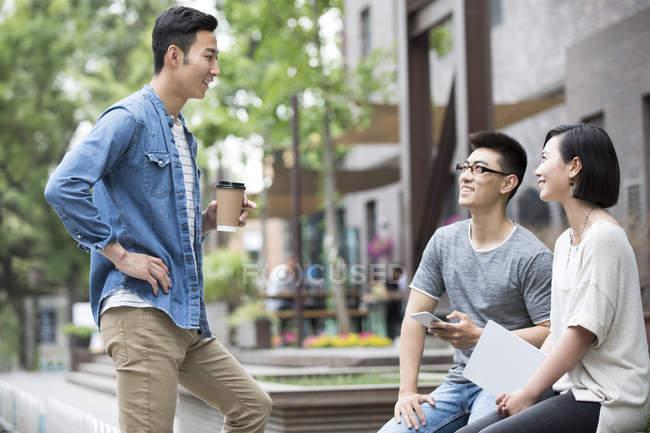 Chinesische Freunde sitzen mit digitalem Tablet und unterhalten sich auf der Straße — Stockfoto