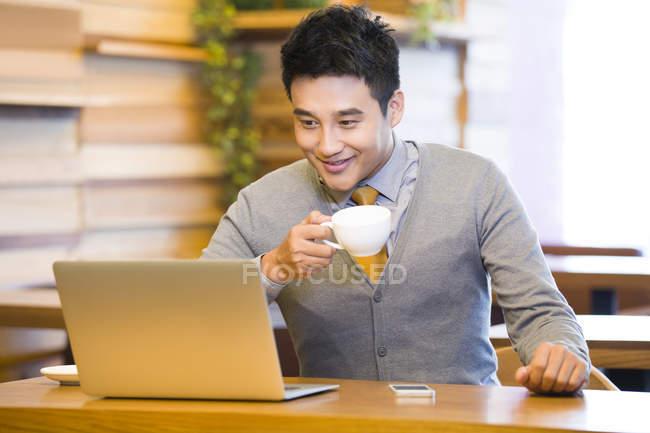 Uomo cinese utilizza laptop e bere caffè in caffè — Foto stock